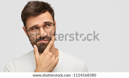 Close up portrait of handsome dark haired male holds chin and looks with hesitsation aside, chooses what to buy between two things, isolaed over white background with copy space for your text #1124568380