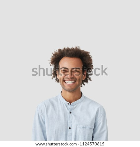 Indoor vertical shot of cheerful mixed race male student with Afro hairdo has broad shining smile, happy to graduate university, dressed in elegant white shirt, poses against blank copy space upwards #1124570615