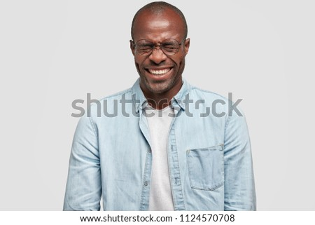 Joyful dark skinned male office worker giggles happily during work break, has fun with friends or colleagues, closes eyes from laughter, dressed in fashionable denim jacket, stands over white wall #1124570708