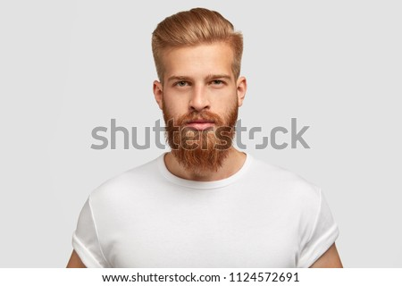 Headshot of red haired serious young male blogger looks confidently at camera, thinks about new content of his web page, dressed casually, earns money distantly, isolated over white background Royalty-Free Stock Photo #1124572691