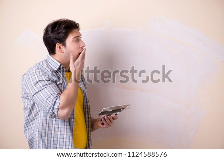 Young man applying plaster on wall at home #1124588576