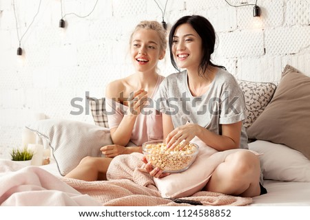 Portrait of funny and happy young women watching comedy in bed and laughing. Cheerful friends eating tasty popcorn and looking movie with gladness. Cozy and friendly atmosphere #1124588852