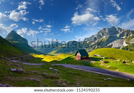 Amaizing sunset view on Durmitor mountains, National Park, Mediterranean, Montenegro, Balkans, Europe.  Bright summer view from Sedlo pass. Instagram picture. The road near the house in the mountains. #1124590235