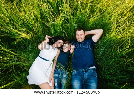 Happy young family spending time together outside in nature on vacation outdoors. Mom, dad and son lie in the green grass. The concept of family holiday. flat lay. top view. #1124603906