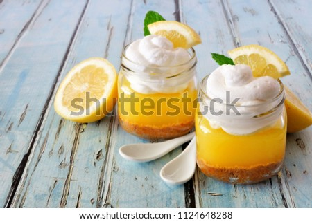 Homemade lemon pie in jars with whipped cream against a blue wood background #1124648288