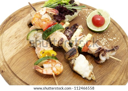 skewers of seafood on a wooden platter in a restaurant #112466558
