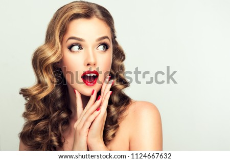 Shocked and surprised girl screaming and  looking to the side presenting  your product . Curly hair woman amazed .Beautiful girl  with curly hair and red nails manicure. Expressive facial expressions #1124667632