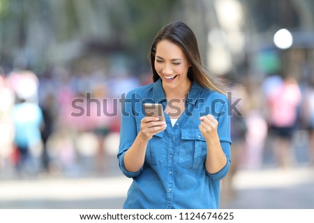 Front view of a excited woman reading good news in a smart phone online on the street #1124674625