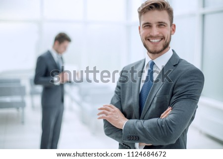 successful businessman on the background of the office #1124684672