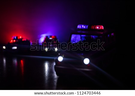 Police cars at night. Police car chasing a car at night with fog background. 911 Emergency response police car speeding to scene of crime. Selective focus #1124703446