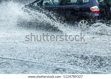 car moving with high speed through water puddle on flooded city road during heavy rain #1124789327