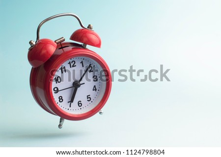 Red alarm clock. Flying alarm clock. Red alarm clock on a blue background.