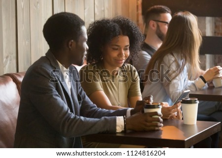 African American couple spending coffee break enjoying favorite drink in paper cup, using gadgets in cozy cafe, multiracial people chilling in coffeeshop, having casual friendly talk. Relaxing concept #1124816204