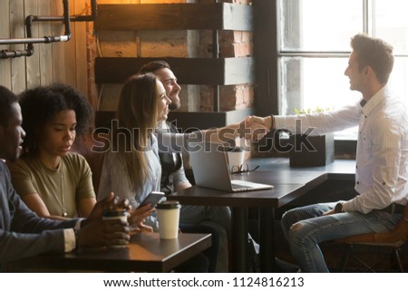 Smiling Caucasian real estate agent shaking hand of satisfied millennial buyers couple, broker closing deal with excited clients at meeting in cafe, realtor handshake greeting customers in coffee shop #1124816213