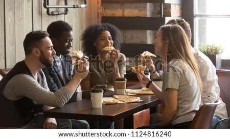 Smiling multiracial friends eating pizza and drinking coffee, laughing and having fun in restaurant, diverse millennial colleagues enjoying lunch during work break sitting at coffee table in loft cafe #1124816240