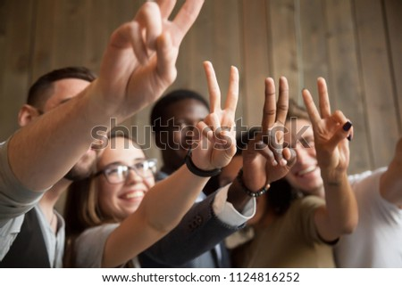 Close up of smiling multiracial people showing V sign making group picture, spending time, having fun together, happy diverse students gesturing victory or peace symbol demonstrating racial equality