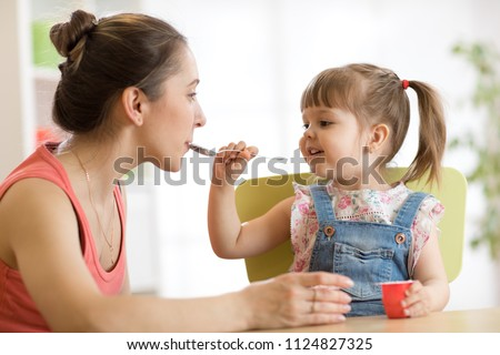 playful child girl spoon feeding her mother #1124827325