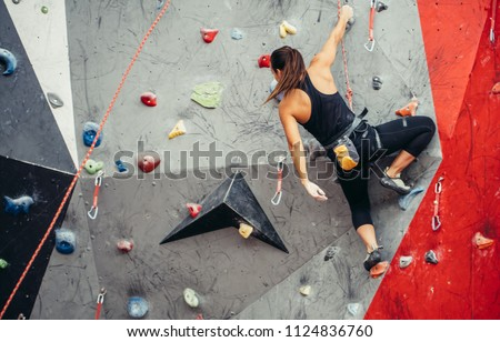 Sporty successful business woman being busy at her hobby-bouldering. Well equipped woman training in a colorful climbing gym, preparing to summer mountain ascend Royalty-Free Stock Photo #1124836760