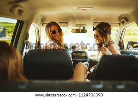 Three women enjoying road trip. They chatting while sitting in the car. #1124906090