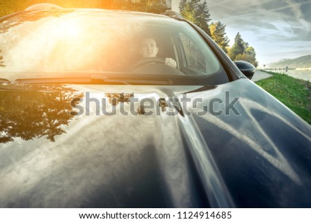 Man sitting in the car and driving in sunny day under sunset sky. #1124914685