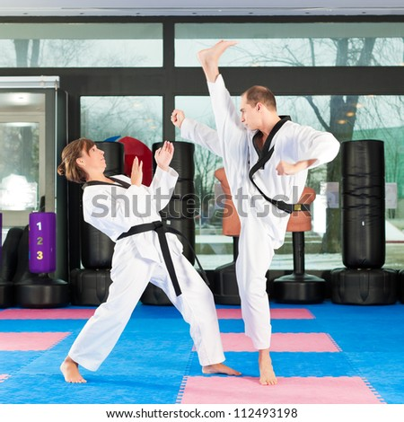 People in a gym in martial arts training exercising Taekwondo, both have a black belt #112493198