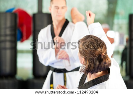 People in a gym in martial arts training exercising Taekwondo, both have a black belt #112493204