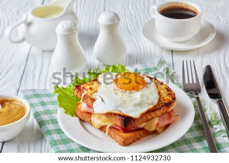 delicious breakfast - hot french toasts croque madame with ham, melted emmental cheese and fried sunny side up egg served on a white plate with cup of coffee on a table, view from above, close-up #1124932730