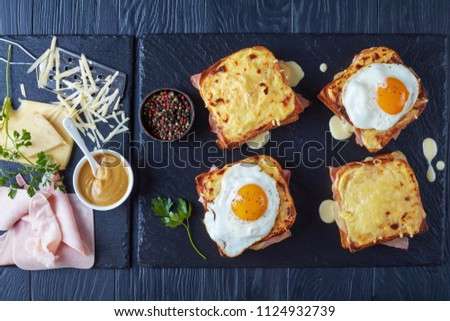 hot french toasts croque monsieur and croque madame with slices of boiled ham, melted emmental cheese and fried sunny side up egg on a stone tray with ingredients on a wooden table, view from above #1124932739
