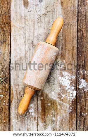Wooden rolling pin with remnants of flour in a rustic kitchen on an old grainy textured wood surface