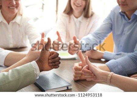 People showing thumbs up at table, closeup of hands. Unity concept #1124953118