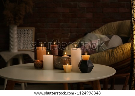 Burning candles on table indoors Royalty-Free Stock Photo #1124996348