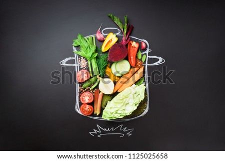 Food ingredients for blending creamy soup on painted stewpan over black chalkboard. Top view with copy space. Organic vegetables, spices, herbs. Vegetarian, vegan, detox, clean eating concept. #1125025658