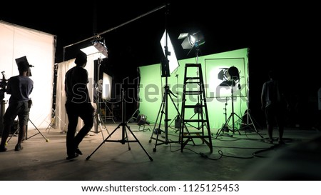 Behind the scenes of TV commercial movie film or video shooting production which crew team and camera man setting up green screen for chroma key technique in big studio. Royalty-Free Stock Photo #1125125453