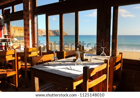 Sagres, Portugal - December 08, 2017: Panoramic view of Sagres beach from inside a restaurant. Bathed by the Atlantic Ocean is one of the most visited by European tourists. Algarve, south of Portugal. #1125148010