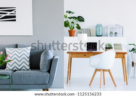 Patterned cushion on grey sofa in scandinavian home office interior with chair at desk. Real photo #1125156233