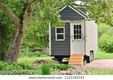 Landscape view of a tiny gray eco friendly house on wheels Royalty-Free Stock Photo #1125182543