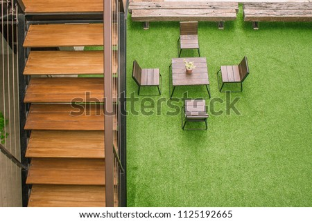 Outdoor Design Concept. Top view of wooden staircase with chairs and desk on green artificial grass in vintage style. (Selective focus) #1125192665