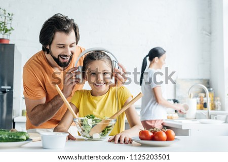 smiling father and happy daughter in headphones cooking together while mother washing dishes blurred on background at kitchen #1125203501