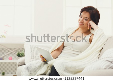 Happy young woman reading on tablet. Smiling girl browsing new messages in social networks, while sitting on sofa, wrapped up in white blanket, copy space. Coziness and technology concept. #1125239441