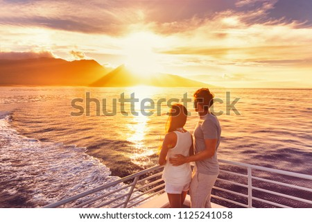 Travel cruise ship couple on sunset cruise in Hawaii holiday. Two tourists lovers on honeymoon travel enjoying summer vacation. #1125241058