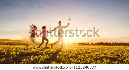 Happy loving family is having fun on nature in the summer. Young mother and two daughters are laughing and playing on meadow at sunset background.  #1125248597