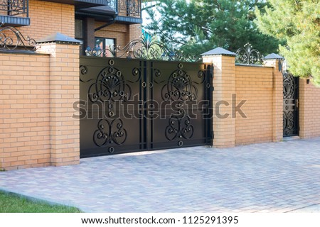Black forged automatic gates in the cottage #1125291395