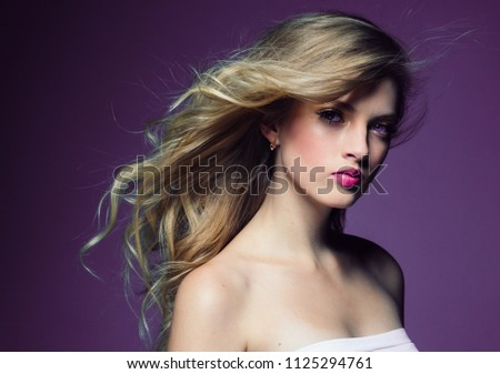Beautiful blonde girl with long curly hair over purple background #1125294761