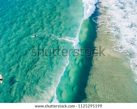 An aerial view of a surfer riding a wave at the beach on the Gold Coast in Queensland Australia #1125295199