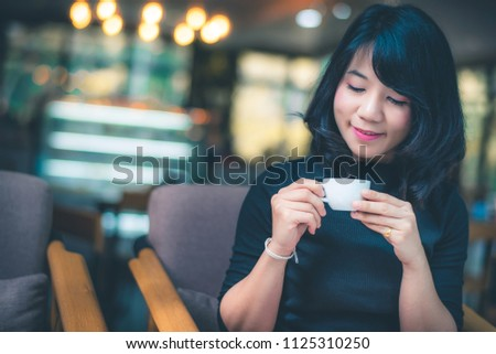Beautiful attractive young Asian woman holding a cup of coffee in hand and sitting on sofa at cafe in the morning, vintage color tone. #1125310250