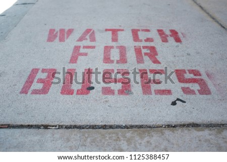 Watch For Buses Sign On The Sidewalk #1125388457