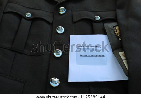 A Police officers black tunic is pictured upon which sits a letter of resignation along with the officers warrant card, signifying the increasing pressure placed upon police and emergency services.