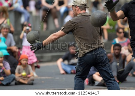 AURILLAC, FRANCE - AUGUST 24: actors playing with heavy balls in the street as part of the Aurillac International Street Theater Festival, show named New town, on august 24, 2012, in Aurillac,France. #112541417