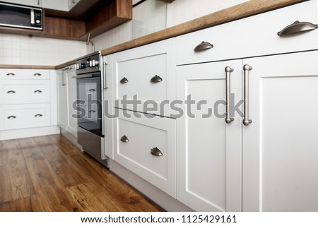 Stylish light gray handles on cabinets close-up, kitchen interior with modern furniture and stainless steel appliances. kitchen design in scandinavian style Royalty-Free Stock Photo #1125429161