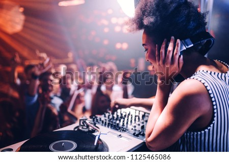Shot of a female DJ playing music in the club Royalty-Free Stock Photo #1125465086